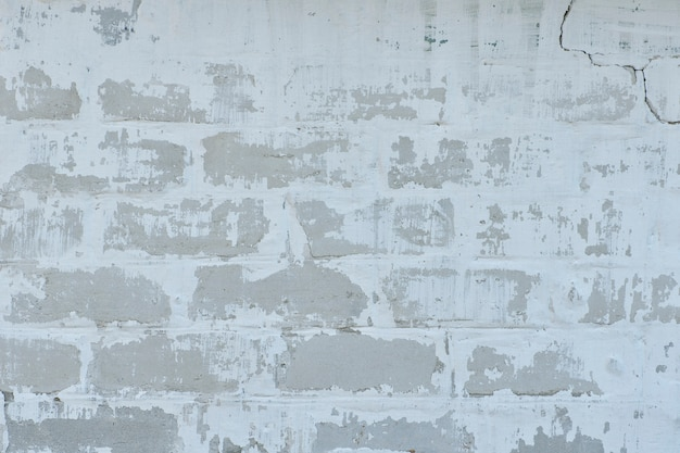 Biały mur z odrapaną farbą.