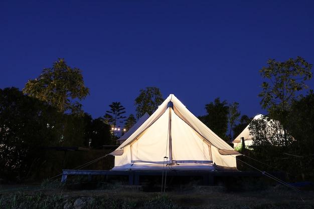 Biały namiot biwakuje nocą w ogrodzie
