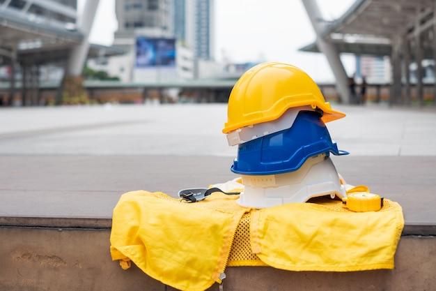 Biały, niebieski i żółty kask ochronny z formalną kamizelką dla pracownika bezpieczeństwa przemysłowego