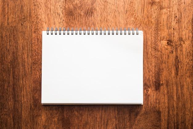 Biały notatnik na antyczne lub wieku drewniany stół