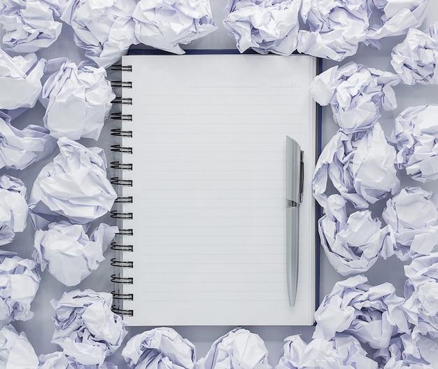 Biały notes na białej ścianie. wokół notatki zmięty papier
