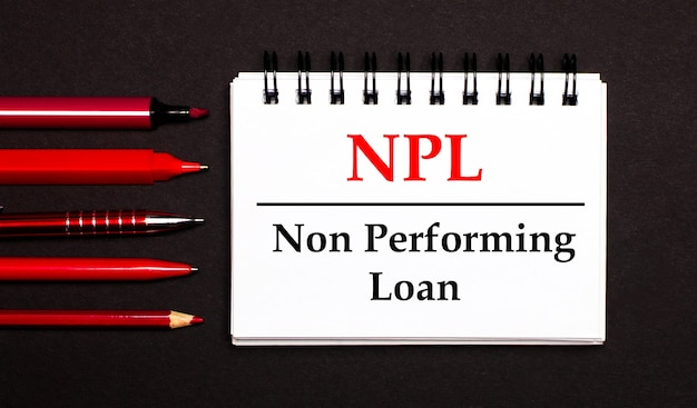 Biały notes z napisem npl non performing loan, napisany na białym notesie obok czerwonych długopisów, ołówków i markerów na czarnej powierzchni