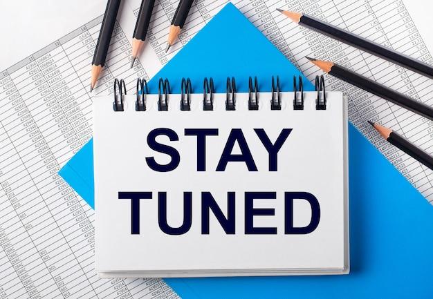 Biały notes z napisem stay tuned na stole obok czarnych ołówków na niebieskim tle i raportów. pomysł na biznes