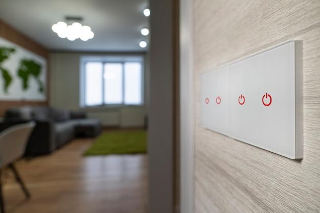 Biały nowoczesny włącznik światła na białej ścianie na tle salonu. nowoczesny design.