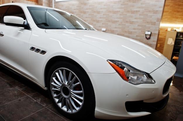 Biały nowy luksusowy samochód sportowy w garażu detailingowym.