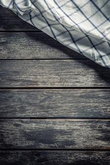 Biały obrus w kratkę na ciemnym drewnianym stole.