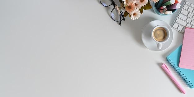 Biały obszar roboczy z widokiem z góry otoczony jest filiżanką kawy i różnymi urządzeniami