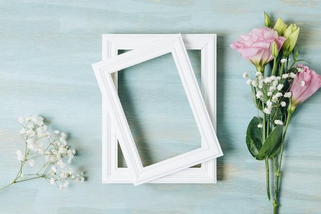 Biały oddech dziecka kwiat i eustoma w pobliżu drewnianej białej ramki na niebieskim tle tekstury