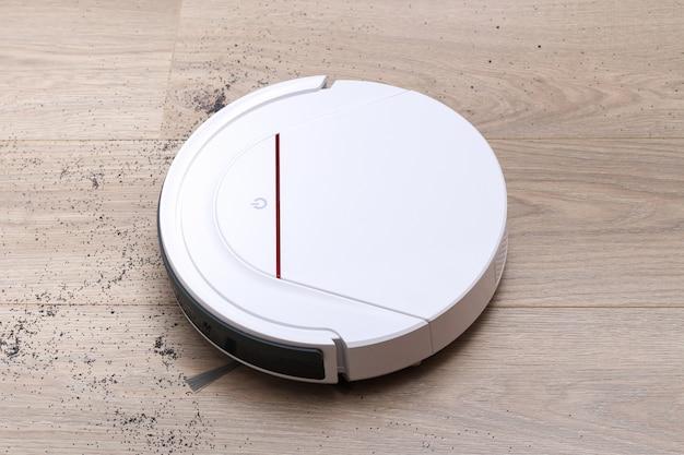 Biały odkurzacz automatyczny usuwa zanieczyszczenia z podłogi laminatu.