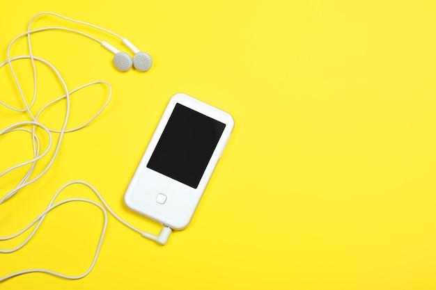 Biały odtwarzacz mp3 i przewodowe słuchawki na żółtym tle.