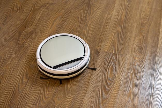 Biały okrągły bezprzewodowy odkurzacz automatyczny na brązowej podłodze laminowanej