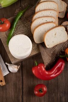 Biały okrągły ser i krojony chleb. widok z góry