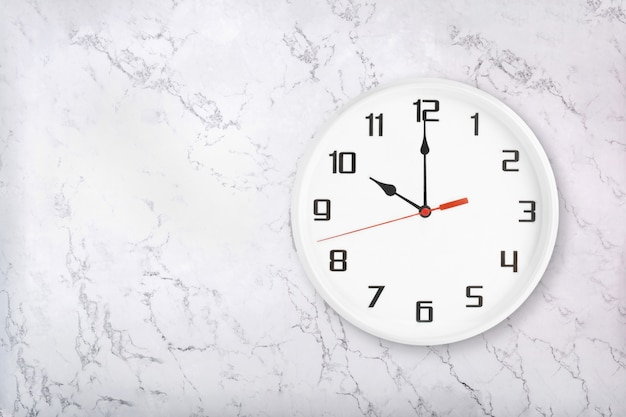 Biały okrągły zegar ścienny na białym tle naturalnego marmuru. godzina dziesiąta