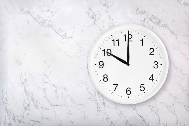 Biały okrągły zegar ścienny na tle białego marmuru