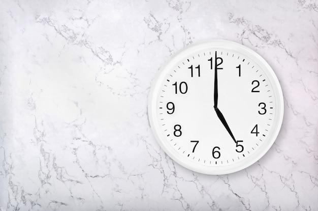Biały okrągły zegar ścienny na tle marmuru. szczęśliwa godzina. koncepcja czasu picia