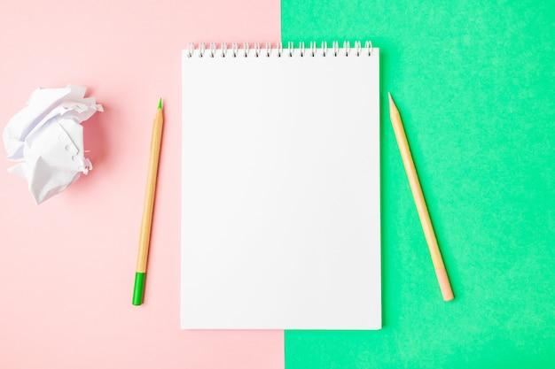 Biały otwarty notatnik na zielonym i różowym tle. w pobliżu znajdują się ołówki.