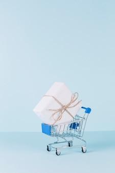 Biały pakunek w wózek na zakupy na błękitnym tle