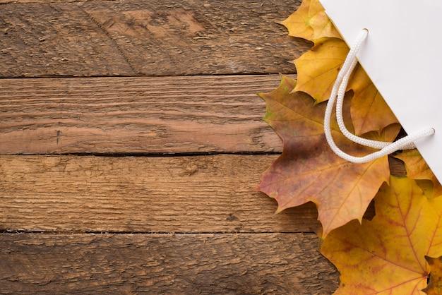 Biały pakunek z jesień kolor żółty suszącymi liśćmi na drewnianym, copyspace. wyprzedaż jesienna