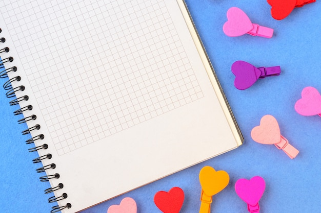 Biały papier i barwioni serca na błękitnym tle. koncepcje notatki na walentynki