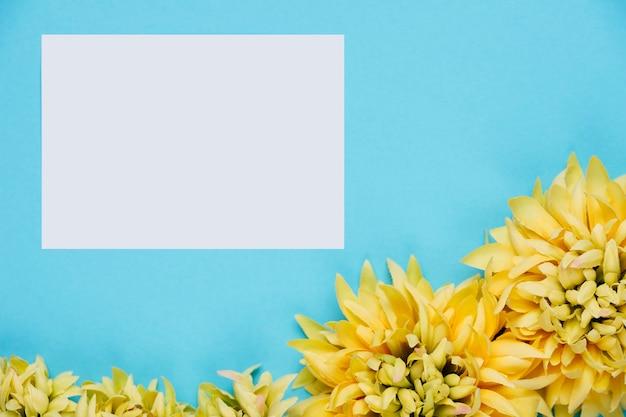 Biały papier na niebieskim tle z kwiatami