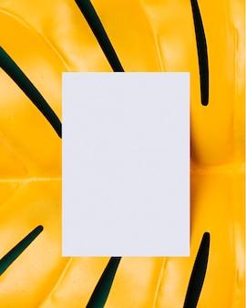 Biały papier na żółtym tropikalnym liścia tle