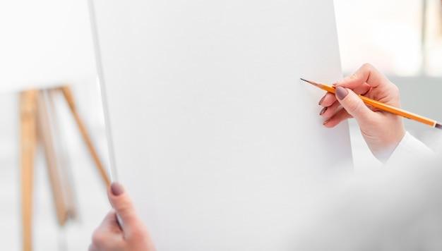 Biały papier płócienny i ręka z ołówkiem graficznym.