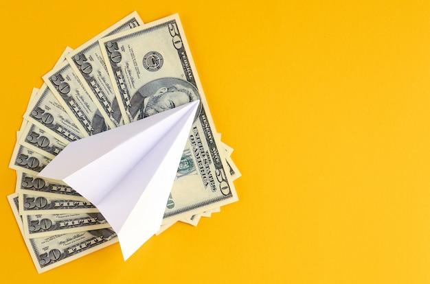 Biały papier samolot i pieniądze na żółtej powierzchni.