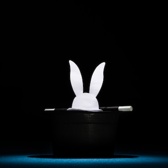 Biały papier wyciął główki królika w górnym czarnym kapeluszu z różdżką