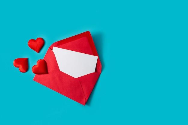 Biały papier z miejsca na kopię w czerwonej kopercie z sercami na niebieskim tle
