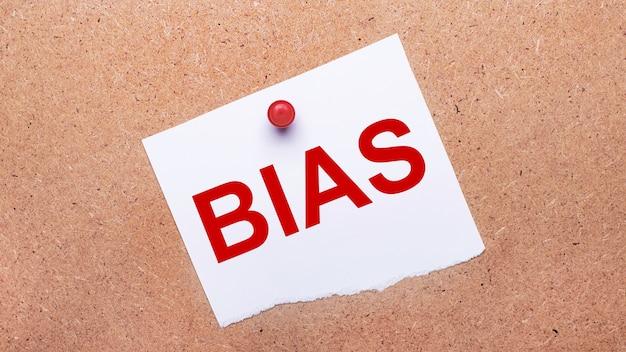 Biały papier z napisem bias jest przymocowany do drewnianego tła za pomocą czerwonego guzika.