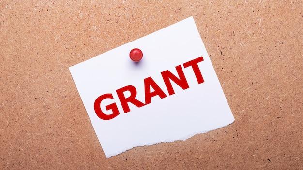 Biały papier z napisem grant jest przymocowany do drewnianego tła za pomocą czerwonego guzika.