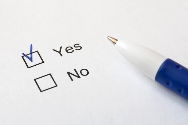 Biały papier z opcjami (tak, nie) i niebieski długopis.