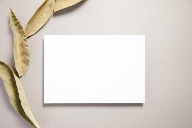 Biały papier ze starymi liśćmi na stole