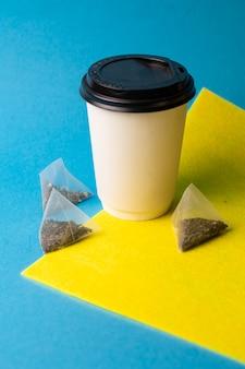 Biały papierowy kubek i torebki herbaty na tle