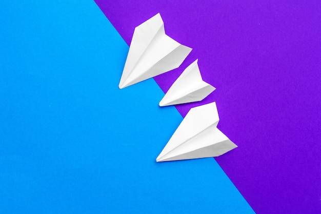 Biały papierowy samolot na bloku koloru niebieskim i fioletowym tle