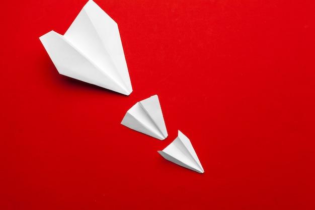 Biały papierowy samolot na czerwieni