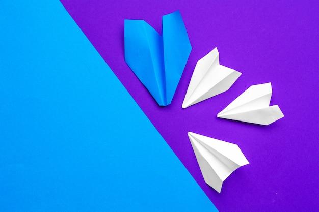 Biały papierowy samolot na niebieskim i fioletowym tle papieru