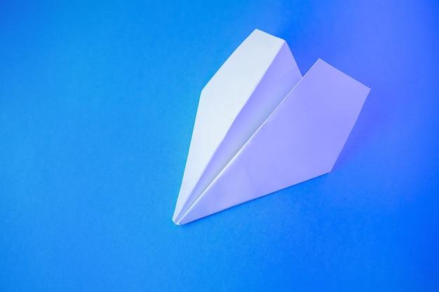 Biały papierowy samolot na niebieskim tle.
