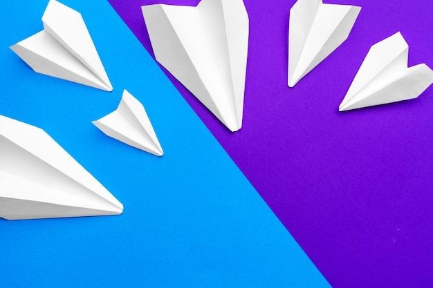 Biały papierowy samolot na papierze niebieskim i fioletowym