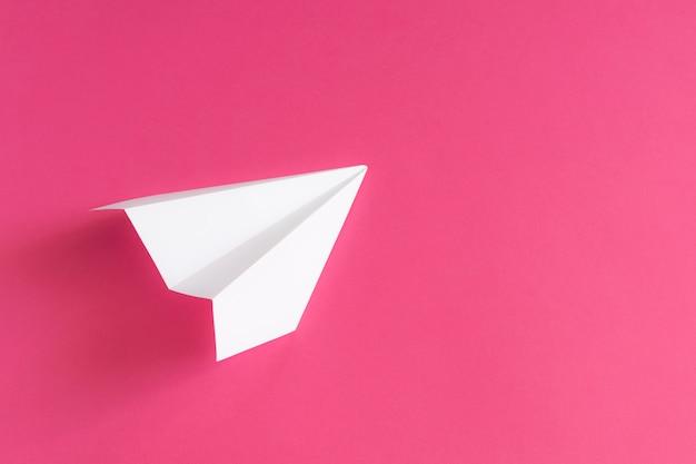 Biały papierowy samolot na różowym tle