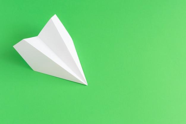 Biały papierowy samolot na zielonym tle