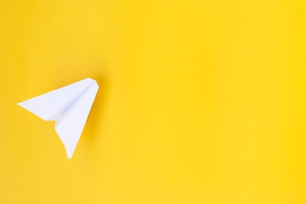 Biały papierowy samolot na żółtym tle. pojęcie