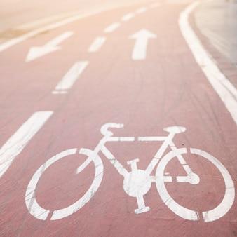 Biały pas asfaltowy rower ze znakiem kierunkowym