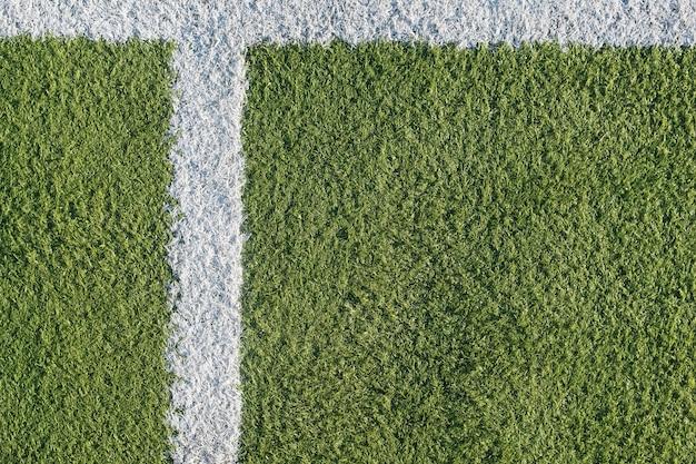 Biały pasek na boisku do piłki nożnej. zielona tekstura boiska do piłki nożnej, siatkówki i koszykówki