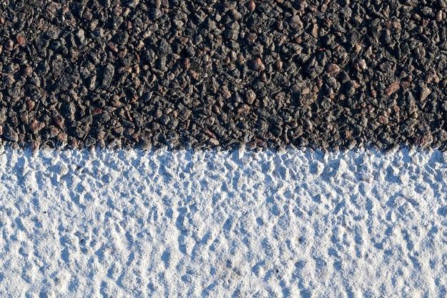 Biały pasek na drodze asfaltowej, aby rozróżnić ruch pojazdów