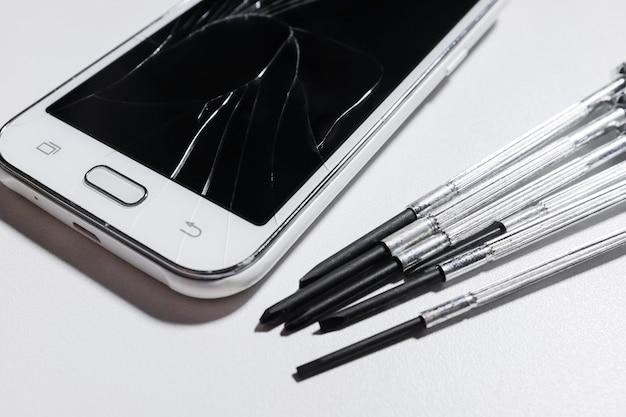 Biały pęknięty wyświetlacz telefonu komórkowego.