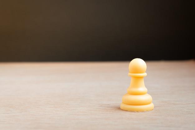Biały pionek szachowy z czarnym tłem