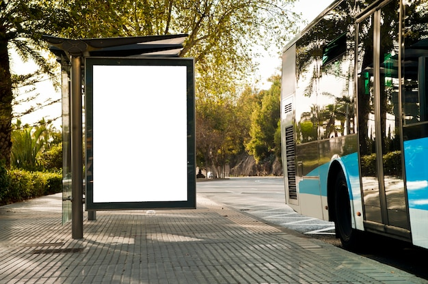 Biały pionowy billboard z autobusem na ulicy miasta