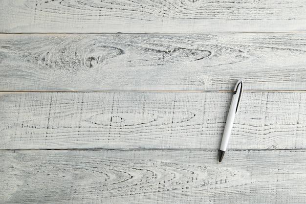 Biały pióro na rocznika podławym białym drewnianym tle. widok z góry. leżał płasko