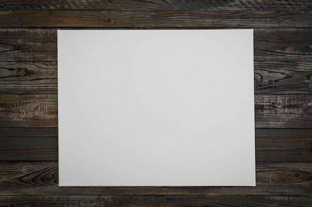 Biały plakat na drewnianym tle